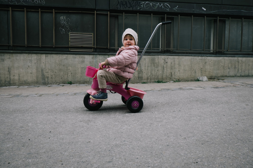 child sitting on a three-wheeler