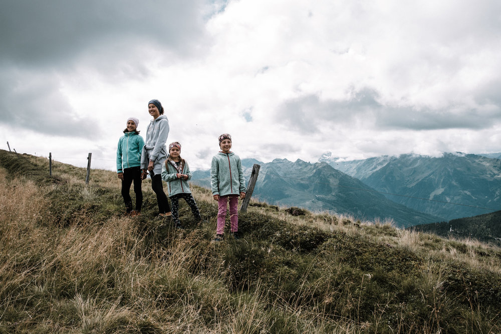 children standing at the ridge of a mountain in a group belonging to a family