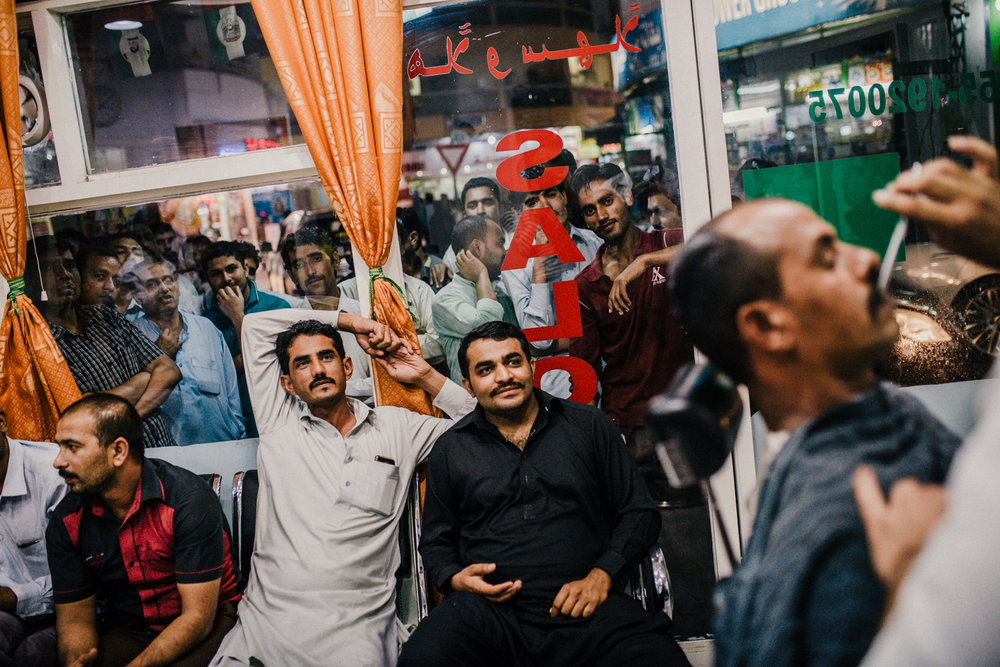 Men stood in and around a barber shop in Naif, Dubai to watch a cricket match on a television in the corner of the room.