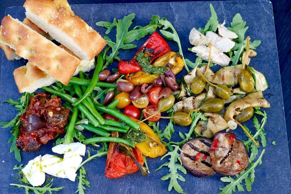VÄRVILINE KÖÖGIVILJAVALIK 12€   Arstišokisüdamed, oliivid, röstitud paprika, marineeritud baklažaan ja suvikõrvits, kapparid, värske basiilikupesto, buffalo mozzarella, aedoad mündi ja küüslauguga, kirsstomatid, Caponata salat, rukola   Tervislik ja värviline snäkivalik, mida Tallinnas suhteliselt harva kohtab (tavaliselt heal juhul ainult juust ja sink valikus). Meie lemmikuteks olid artišokisüdamed, marineeritud baklažaan ning suvikõrvits, mis oli kaetud mõnusa tomatise kastmega. Tõeliselt kerge ja suvine roog, mis ei pane ka oma vööümbermõõdu pärast muretsema. Kui sina oledki see sarisnäkkar, kes pidevalt midagi mäluda tahab, siis isutekitajaks on see parim valik! Haara vein või mõni muu meelepärane jook ja mine naudi seda oma sõbra(nna)ga armsal lilledega kaetud terassil. Soovitame!