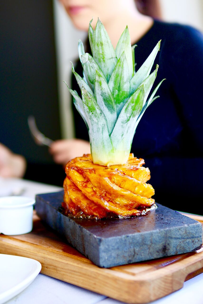 KARAMELLISEERITUD ANANASS 2-LE 10€   Kookose sorbee   VÄGEV! Kui soovite naistelauas elevust tekitada, siis üks särisev laavakivialus ja karamelliseeritud ananass tekitavad sädistamist pikemakski. Aurav ja särisev ananass otse su silme all. Jällegi oli kõik detailselt läbi mõeldud - ananassi juurde toodi külm kookosejäätis ja siirup ning kui need kolm korraga suhu panna tuli sellest välja eriti hea piña colada. Sellest ei saanud me küllalt. Tõeliselt positiivne magustoidu elamus. Soovitame!! Ja muide, ka neljakesi saab seda toredat kombot süüa.