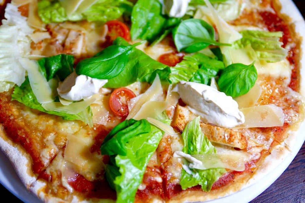 """....  Caesari Pizza 7,9€   Kodune tomati kaste, mozzarella, kanafilee, suitsutatud peekon, parmesan, roomasalat, Caesari kaste   Nimi tundus üsna atraktiivne ja see tegi proovimise lõbusaks. Keskelt oli pitsa mõnusalt mahlane ja pehmuselt juba pitsapõhja mõistes suht """"well done"""", äärtest krõbedam ja seepärast ka kergemini käes hoitav (õige pitsa söömine käib ikkagi kätega). Isenesest ei olnud pitsal midagi viga, kuid caesari kaste oli asetatud pitsa pinnale pisut ebapraktiliselt - seda oleks tulnud pahteldajaga laiali ajada. Teiseks oli kaste rammusalt majoneesine ja see langetas arvamust pitsast, aga pitsa on pitsa. Alles me seda loomulikult ei jätnud.  ..  Caesar pizza 7,9€  The name of the pizza seemed quite attractive for us, which made tasting the pizza quite exciting. From the center, the pizza was juicy and the crust was crunchy as it should be, which made it easier to hold (of course we ate pizza with our hands). It was a decent pizza, but we had a problem with the Caesar sauce, which was placed on the dish in clumps. This meant that we had to individually spread the sauce allover, which just didn't make sense to us(some pieces had a big clump of the sauce and the other none at all). Secondly, the sauce had way too much mayo inside, which we didn't like too much. It wasn't a bad pizza, but we recommend you try something else, there is much better stuff in the menu than this pizza!  ...."""
