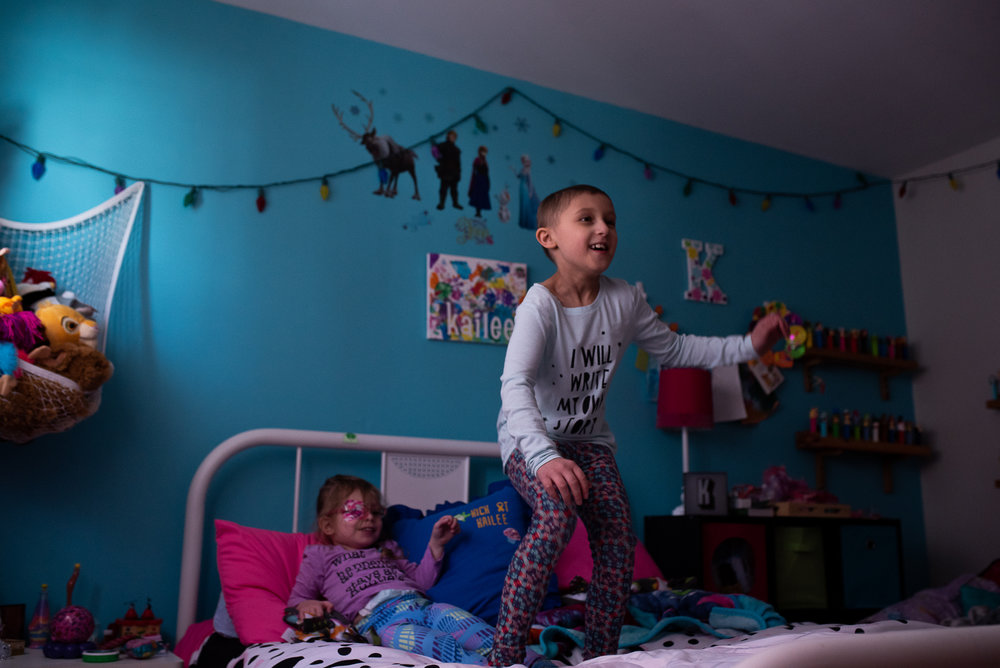 Kailee jumps on her bed with Morgan, Kailee's younger sister on St. Patricks day at their home. Morgan has only known Kailee with cancer. Catherine found out she was pregnant with Morgan just weeks after Kailee's initial diagnosis in 2013.