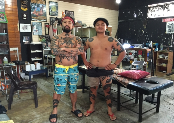 Jeremy Lo (left), and Jesse (right) continuing work on the full-body Iban tattoo of the Kapit area. The famous  Bunga Terung  tattoos are found on their shoulders.