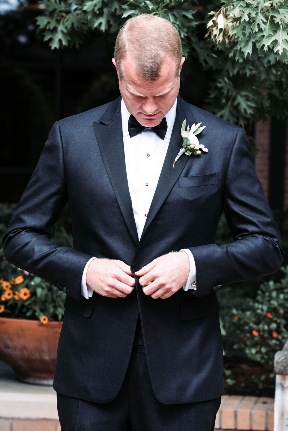 Wedding portrait groom suit boutonnière bow tie