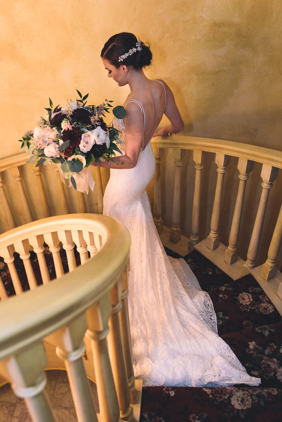 Elegant bride descending spiral staircase with bouquet