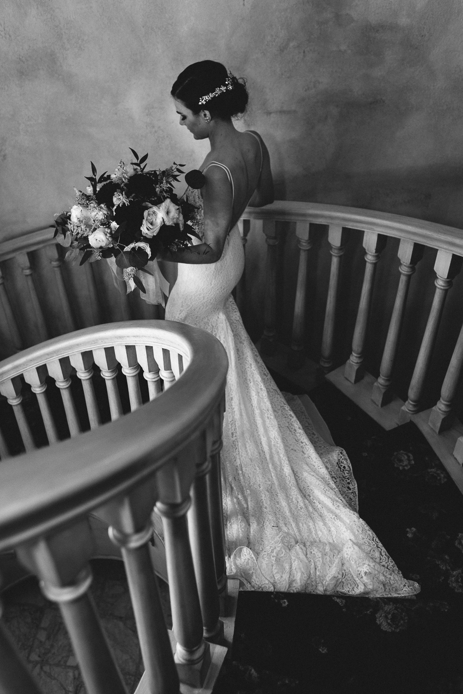 elegant bride descending spiral staircase with bouquet black and white bridal portrait