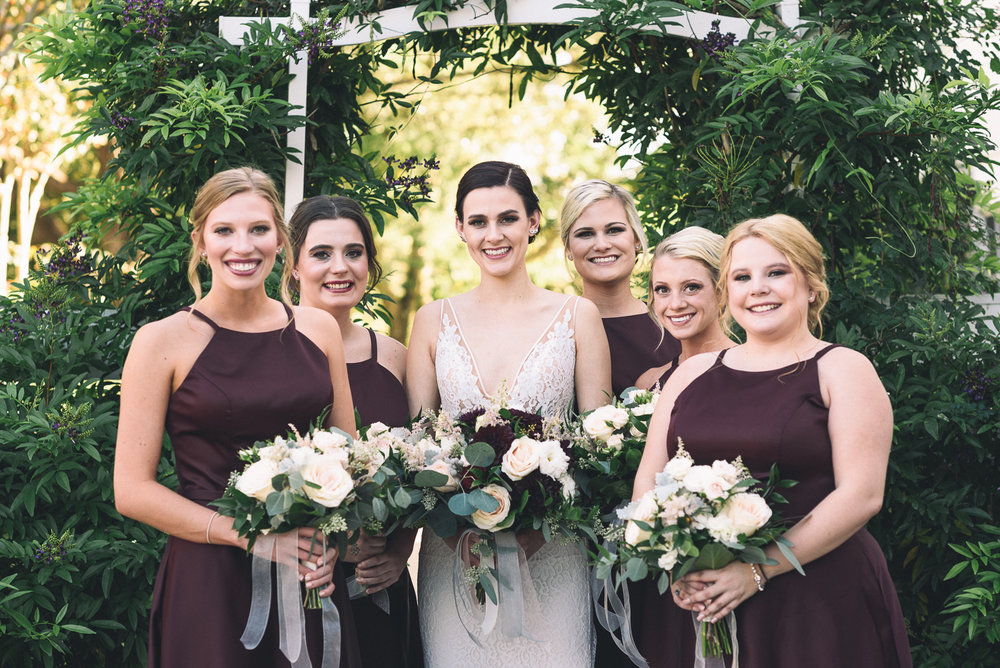 brides maids portraits fancy dresses pretty flowers smile vine archway