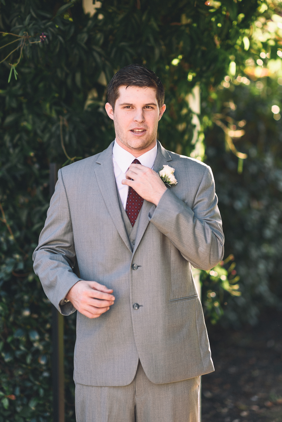 groom portrait maroon tie grey suit boutonniere
