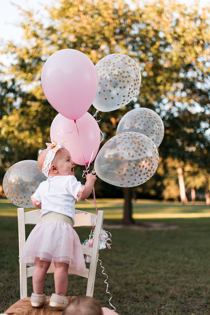 Pink lifestyle photography twins first birthday balloons park