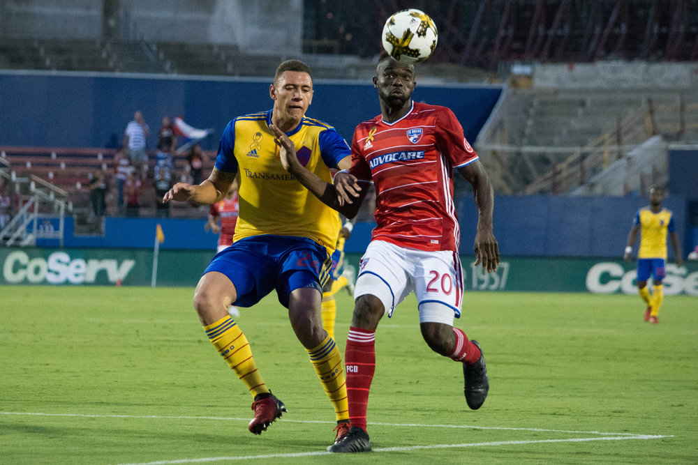 Rapids Defender Kortne Ford and FC Dallas Midfielder  Roland Lamah  track down a ball.