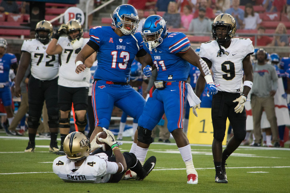 SMU's Tyson Neals and Kyran Mitchell celebrate after a huge hit on UCF's Tre'Quan Smith.