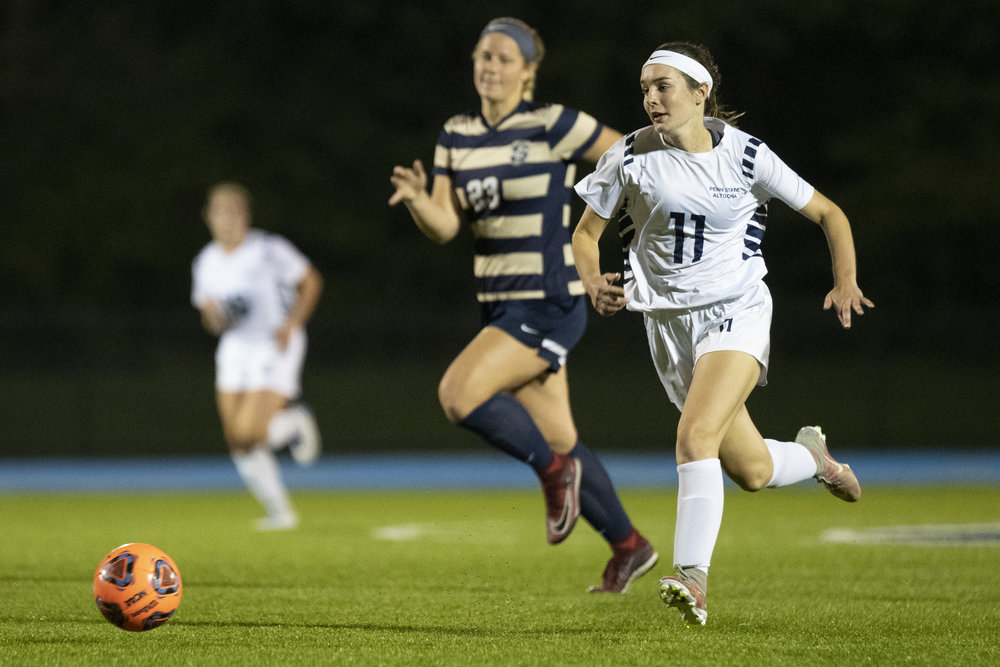 Penn State Altoona Women's Soccer player Sadie McConnell (#11) on a breakaway run as Juniata College player Kristin Racis (#23) follows close behind in Altoona's 4-1 win against Juniata College on Wednesday, September 19th, 2018 at Spring Run Stadium. - Photo By: Noah Riffe