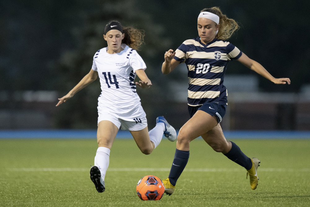 Juniata College Women's Soccer player Alexis Ulrich (#20) dribbles the ball past Penn State Altoona player Alana Masullo (#14) in Altoona's 4-1 win against Juniata College on Wednesday, September 19th, 2018 at Spring Run Stadium. - Photo By: Noah Riffe