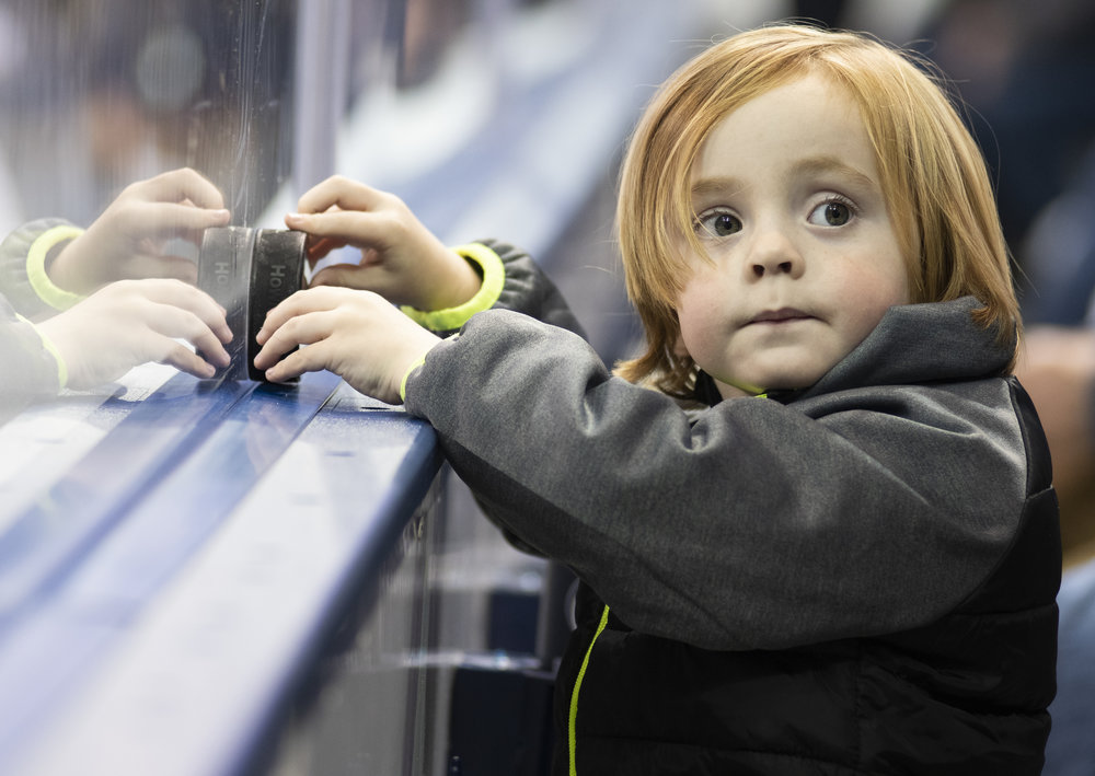 A young fan plays with a puck during game against Arizona State at Pegula Ice Arena on Saturday, Nov. 3, 2018. The Nittany Lions fall to Arizona State 4-3 in overtime. | Photo by: Noah Riffe