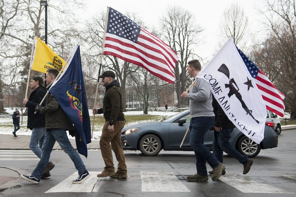 Protesters march down West College Ave. holding flags for the Come and Take It, Hogg protest at the Allen Street Gates on Friday, Jan. 18, 2019. - Photo by: Noah Riffe
