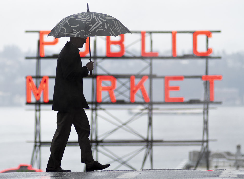Man crosses street in front of Pike Place Market's Public Market sign on Wednesday, March 6, 2019 in Seattle, Washington.