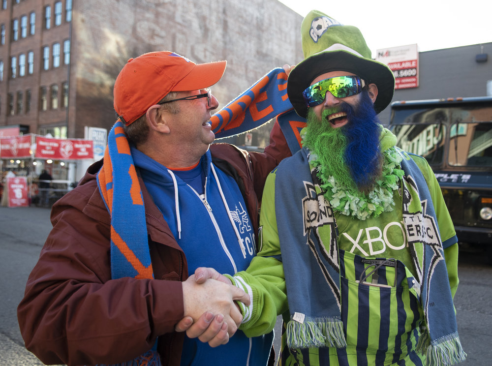 Two opposing fans shake hands while FC Cincinnati fans march to the Seattle Sounders FC vs. FC Cincinnati match on Saturday, Mar. 2, 2019 at CenturyLink Field in Seattle, Washington. | Photo by: Noah Riffe