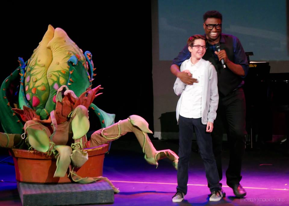 Audrey II (Puppeteer Marc Petrosino), Seymour (Jackson Davis) and host + Executive Producer, Michael-Leon Wooley sing from Little Shop of Horrors.