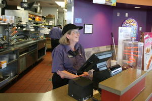 Miss Carol stands behind the Nicholasville, Ky. Taco Bell's cash register. (Photo by Mike Moore, The Jessamine Journal)