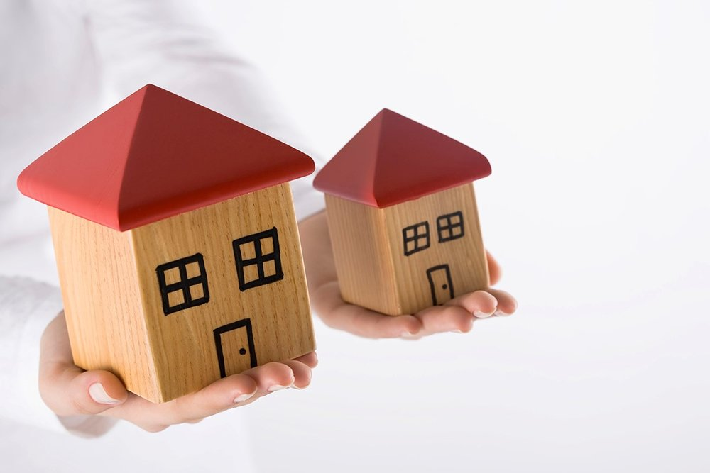 Large house and small house in the palm of two hands