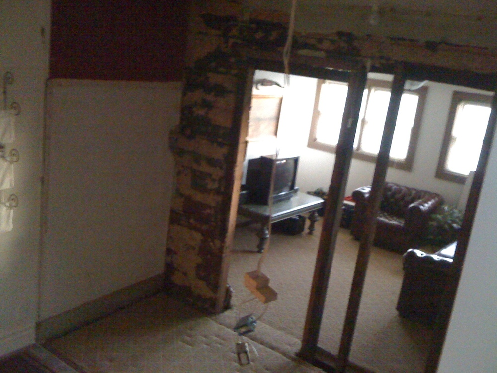 b4: standing on the original stairs in the side entryway, you can see we already removed one wall (far left you can see transition from tile to tan carpet), which was the closet to this room. In the middle of the picture, we tore off the drywall so you can see into what will become the dining room.