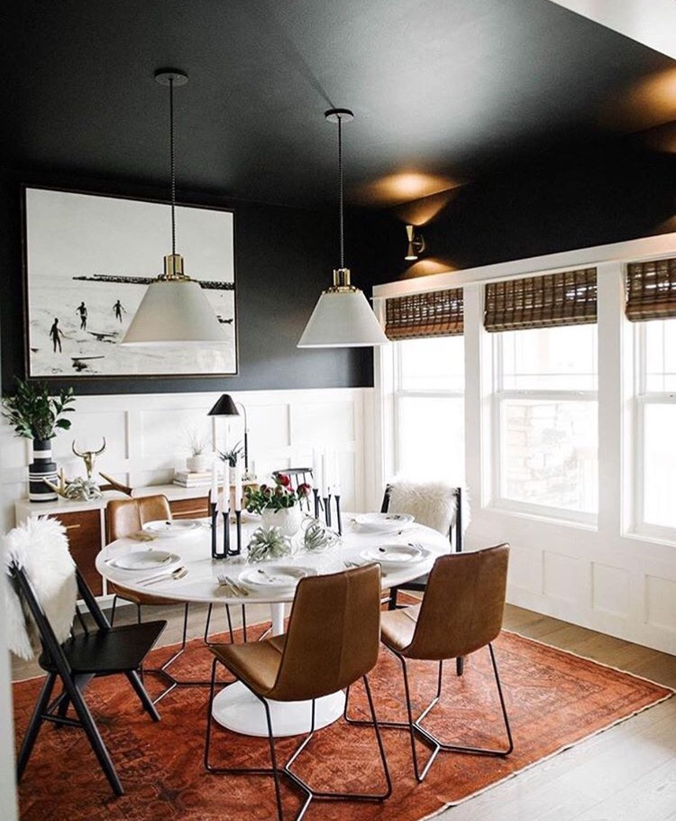 1. Wall Color   Painting your entire room black creates a bold dramatic look that we're all for. But if you don't feel comfortable committing to that much black, consider painting just your ceiling and upper part of your walls. Pair it with white wainscoting for a crisp textural layer that'll help brighten up the space. Make sure to carry white throughout the room to balance the black and white combo. Have fun with textures like they did here with the chair furs and table. Then to make sure the room doesn't feel like it's toppling over, bring white up to the top of the room like you see here with the artwork and pendant lights. Layer the room with a bold rug to give the space a pop of color.