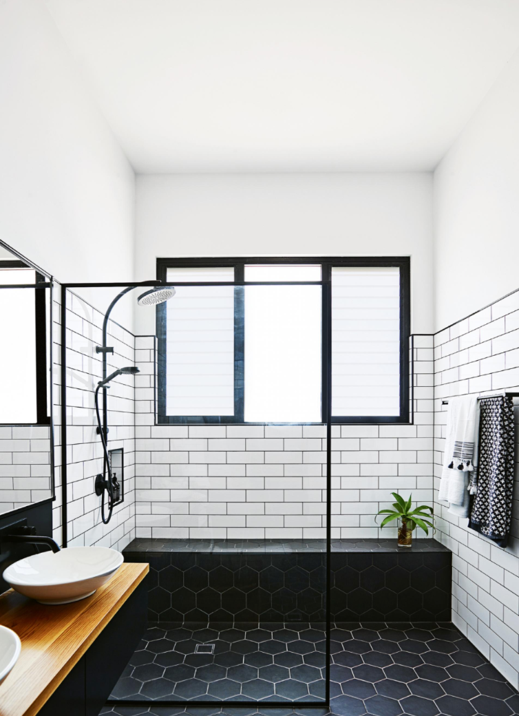 "2. Tile   Try tiling your bathroom floor in black, like here with a 8"" hexagon shape. We love how they used white grout to give it another layer, and created a smooth transition between the shower and rest of the bathroom floor. This seamless look makes the floor the focal point of the room. Bringing in a wood countertop and plant softens the look."