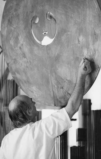 Bertoia using an implement he made to play a bronze gong,  1975. Photo by and courtesy of Beverly H. Twitchell
