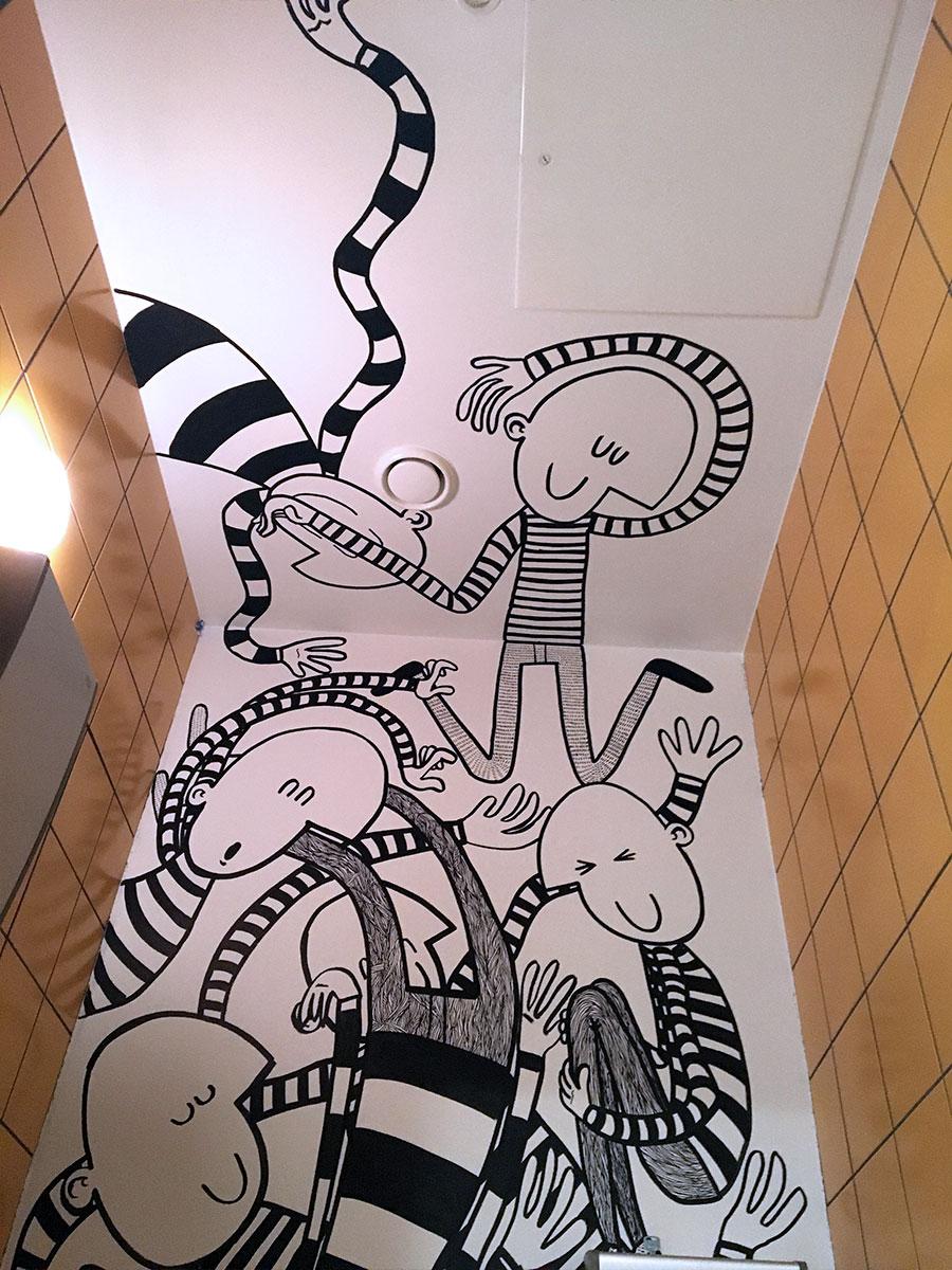 Noen av figurene befinner seg på både den ene og den andre siden av veggen som skiller to av toalettene.