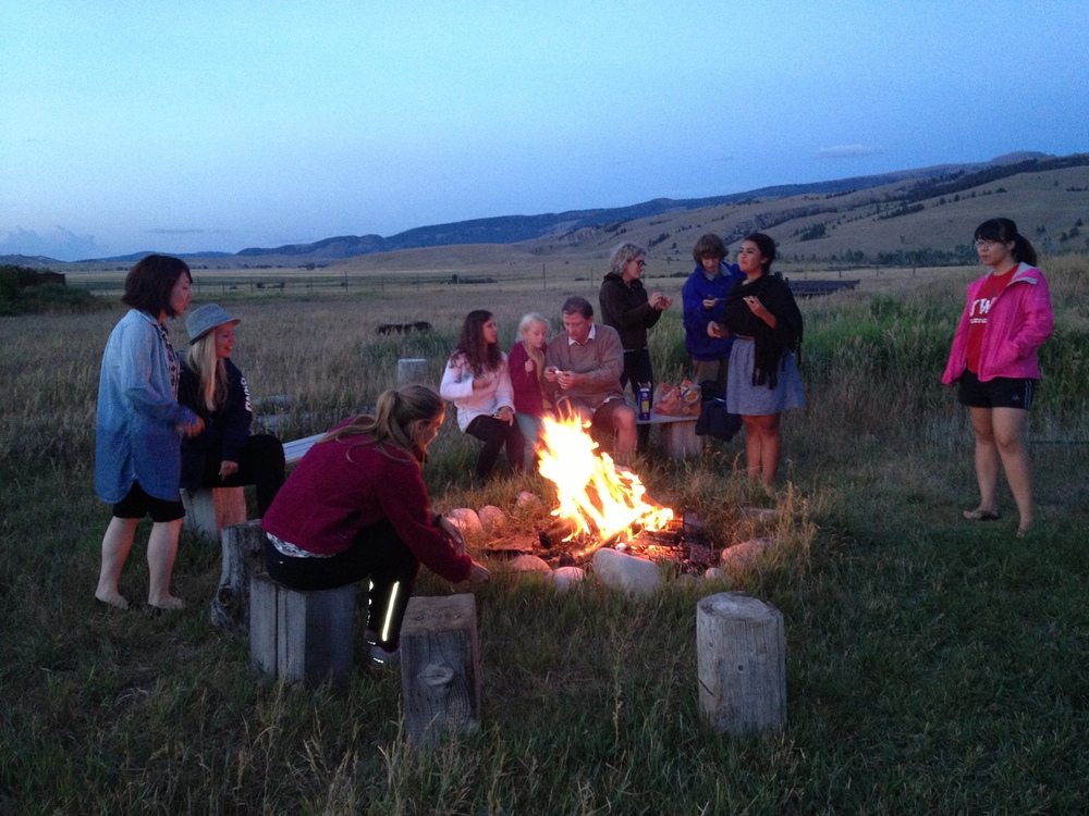 Friends around the campfire looking to the Grand Tetons.