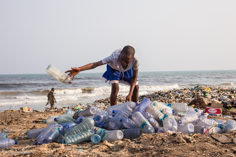 A young boy sorts through plastic bottles picked from the ocean. Accra, Ghana. 2017