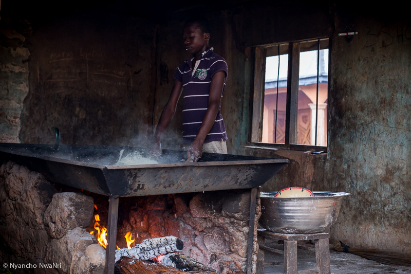 Joseph processes ground cassava over a traditional oven. Benue, Nigeria. 2017