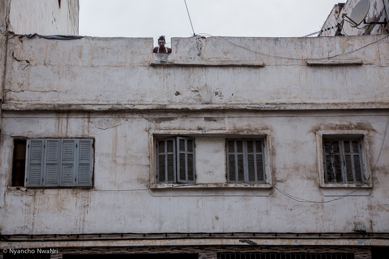 A resident peeks out over the rooftop of a communal building. Casablanca, Morocco. 2017