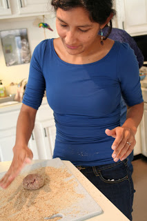 Massage salt and pepper into ground beef with your hands. Then you divide the ground beef into balls the size of limes. On top of a pile of breadcrumbs sprinkled with ground pepper, pat the first meatball into a patty.