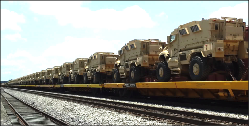 MRAP military vehicles being hauled by train in California.