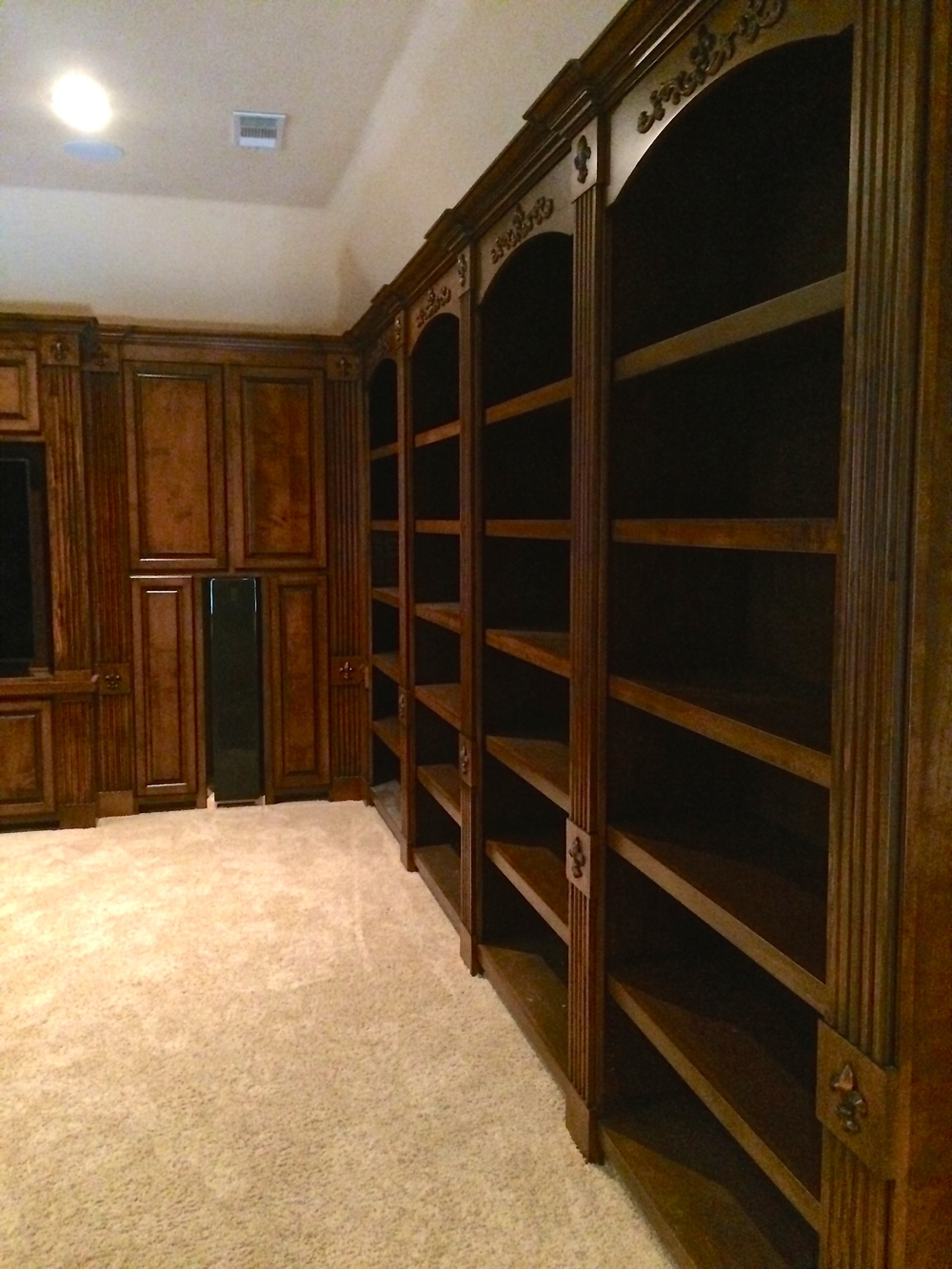 Traditional Curved Top Bookcase with Applied Carvings, Adjustable Shelves, and Fluted Pilasters