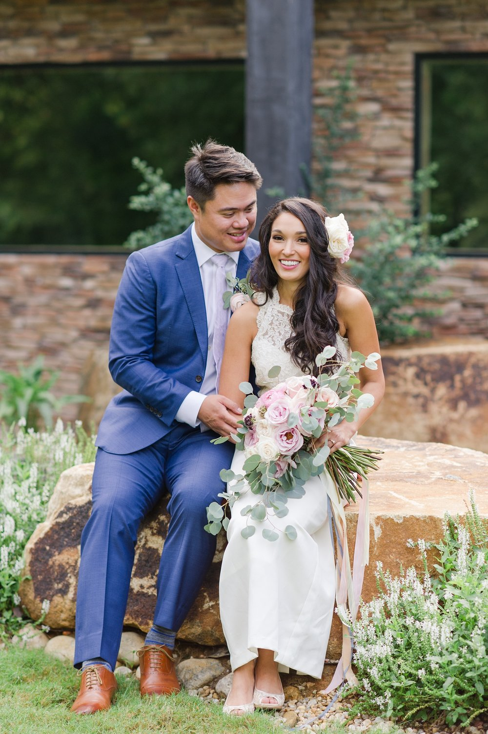Styled Shoot photo of a bride and groom sitting with loose organic bouquet and a blue suit
