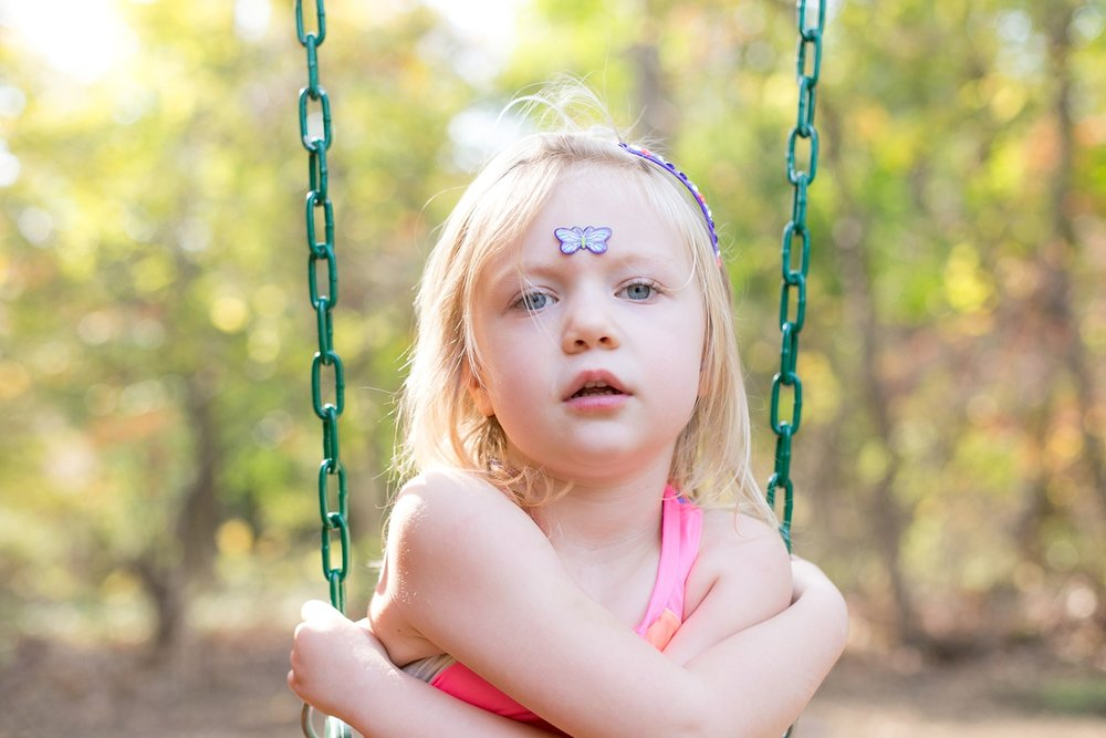 backlit young girl on a swing with a butterfly on her forehead