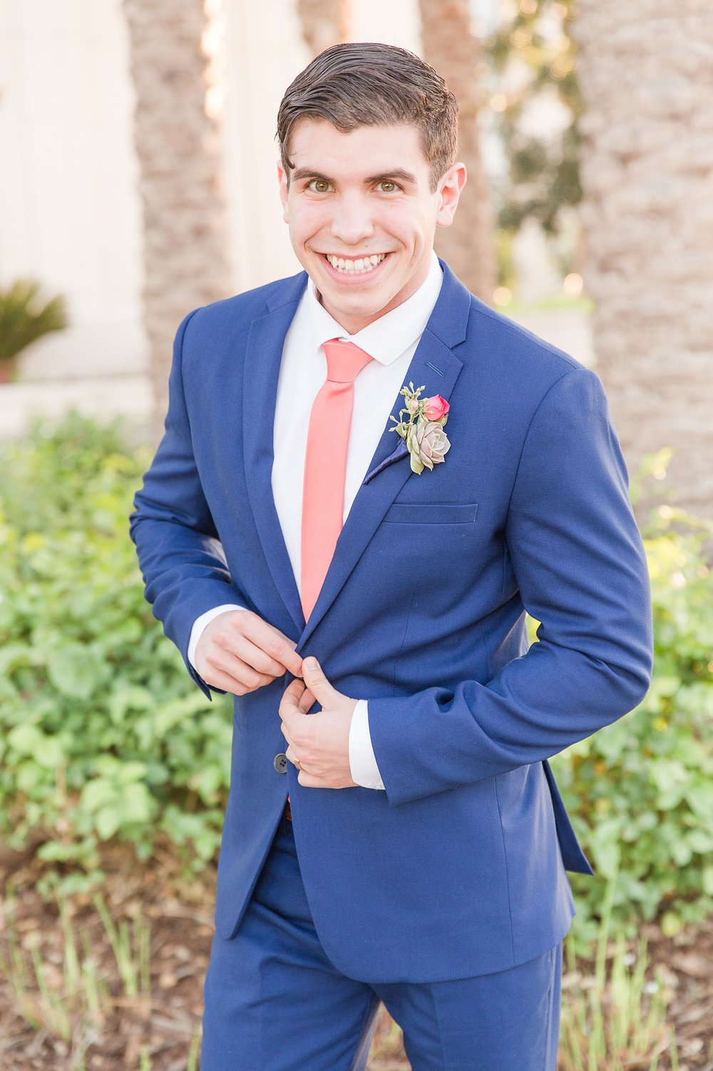 Groom in a blue suit and a pink tie smiling at the camera
