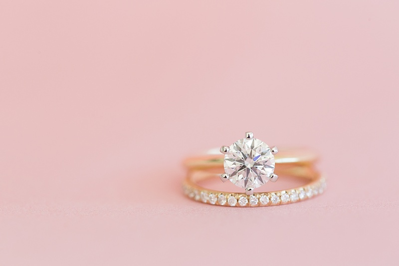 gorgeous diamond wedding ring and band on pink surface
