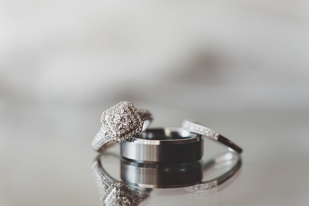 diamond engagement ring, wedding band and grooms band sitting on a mirrored surface