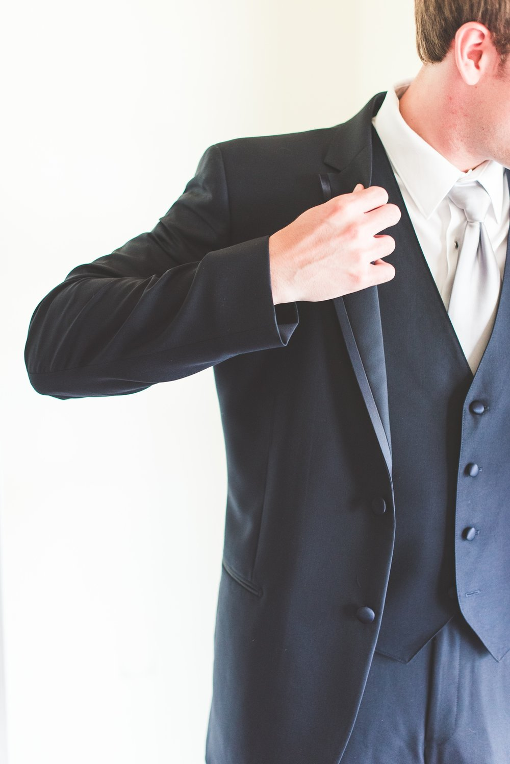 image of groom putting on his jacket getting ready for his wedding