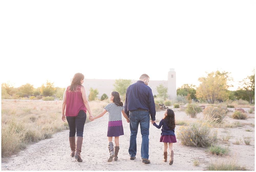 Family of four dressed in blue and maroon walking into the sunset | Running a family photo session