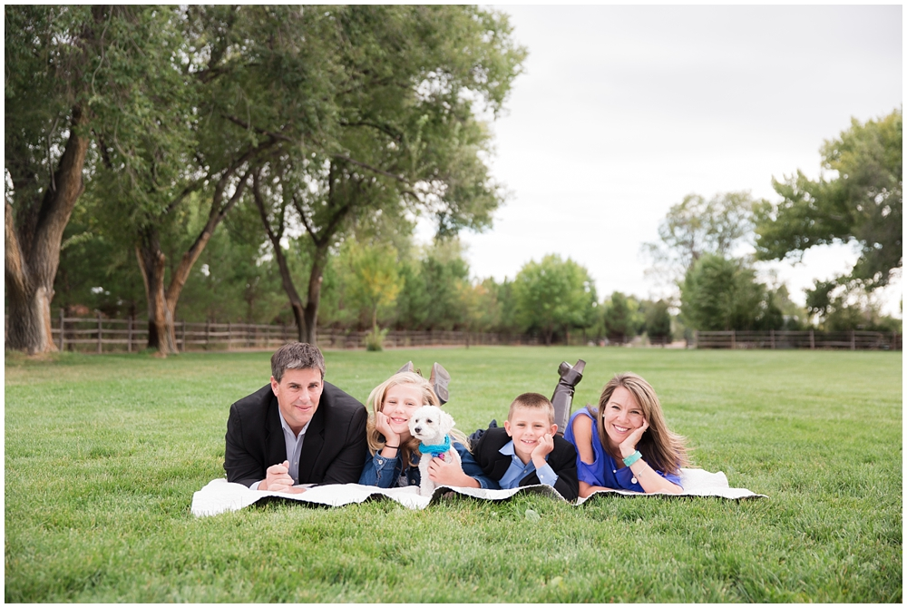 Family of four with dog laying in green grass with trees behind | How to run a great family photo session