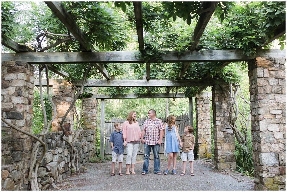 Stylish family of five holding hands under a pergola | Running a successful family photo session