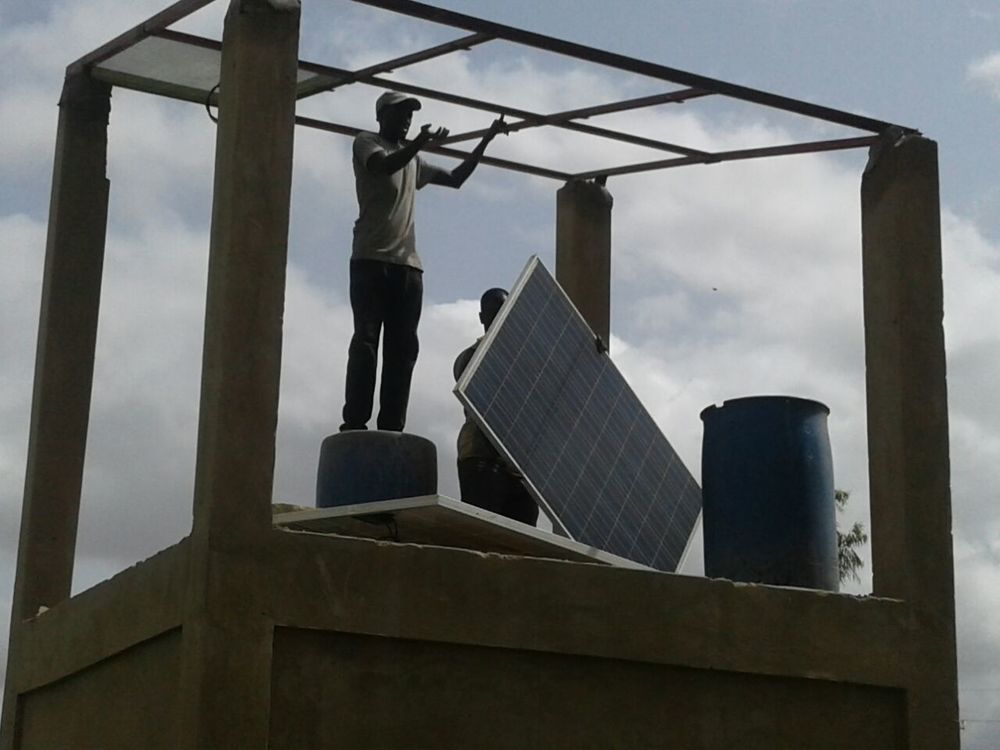 Installing the solar panels on top of the pump housing/tank support structure.