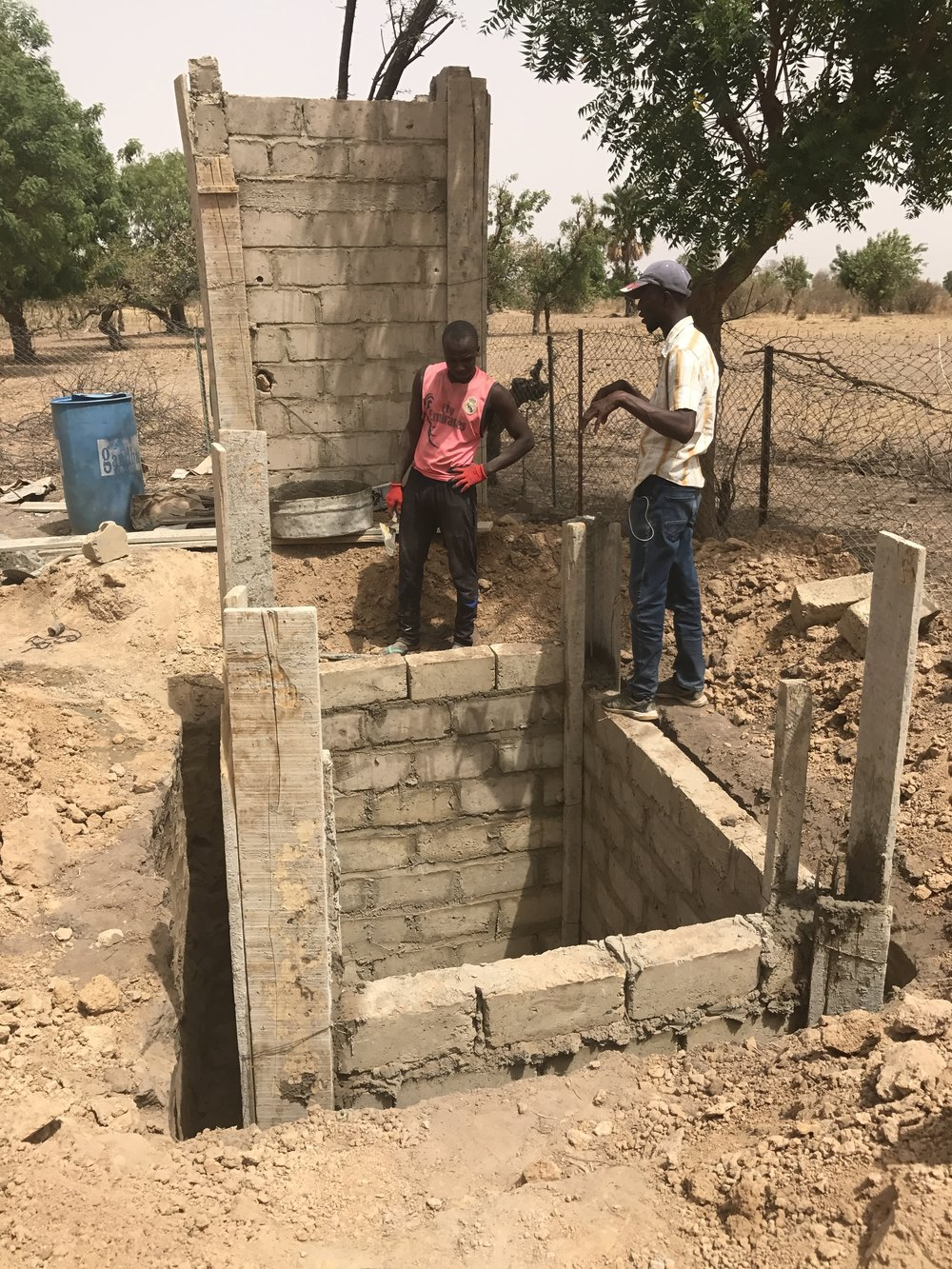 Lead Contractor Abdoulaye Kane (right) going over construction of the latrine at the Kouthieye Market Garden. When the gardens are some distances from surrounding homes, we build a latrine that the women can use when working at the site.