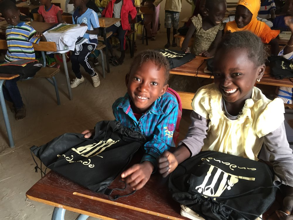 Happy students receiving new school supplies at one of our partner schools.