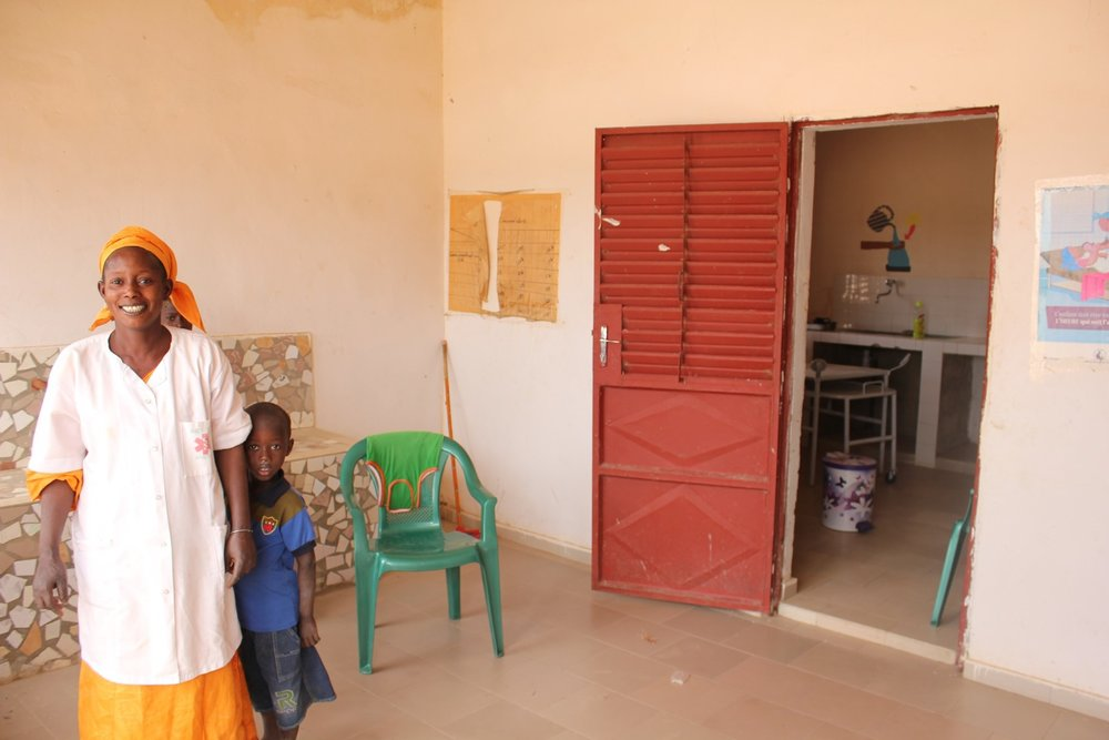 A midwife proudly standing in the waiting area of a newly opened health post.
